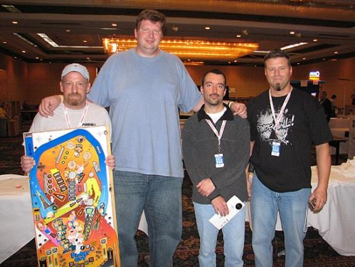 MacCulloch (in the blue) has made some new friends playing pinball.  (Pic via pinballnews.com)